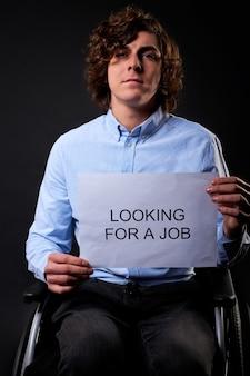 Mann sitzt mit arbeitssuchpapier ernsthaft und sucht einen job. isolierte schwarze wand