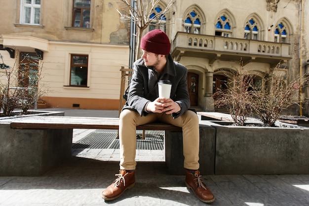 Mann sitzt mit tasse kaffee draußen an einem sonnigen tag