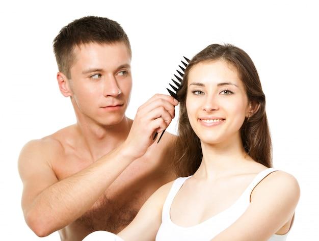 Mann sitzt neben einer frau und kämmt ihre haare