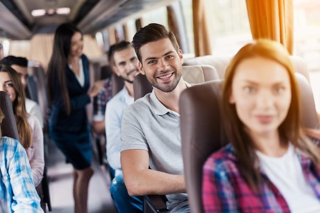 Mann sitzt und lächelt um sie sitzen die anderen passagiere