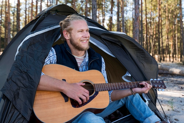 Mann sitzt und spielt gitarre