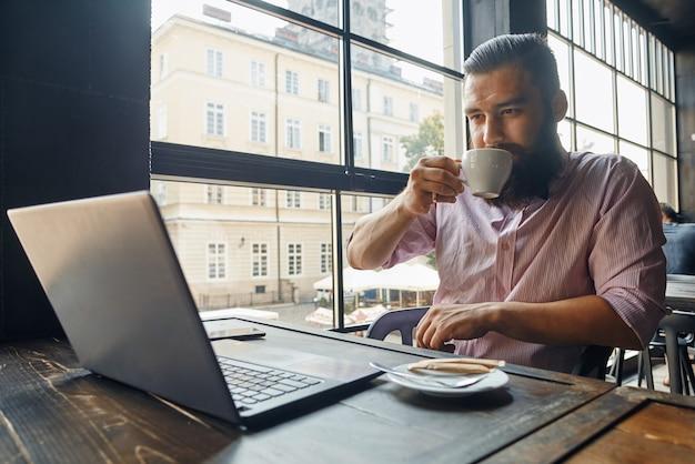Mann sitzt vor dem computer und trinkt kaffee