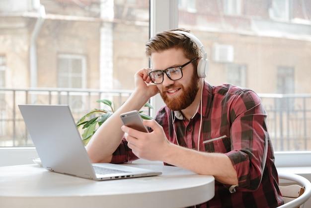 Mann sms auf smartphone beim musikhören
