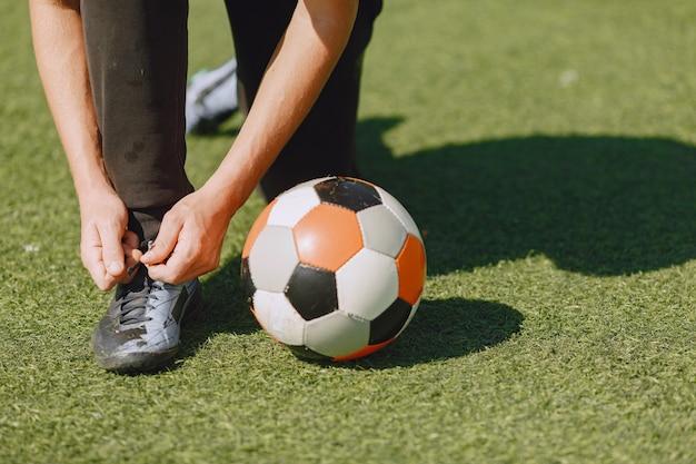 Mann spielen socerl im park. turnier auf mini-footbal. kerl in einem schwarzen sportanzug.