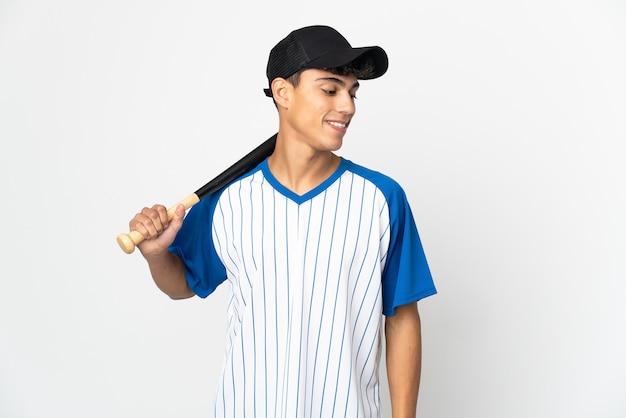 Mann spielt baseball über isolierte weiße wand, die seite schaut