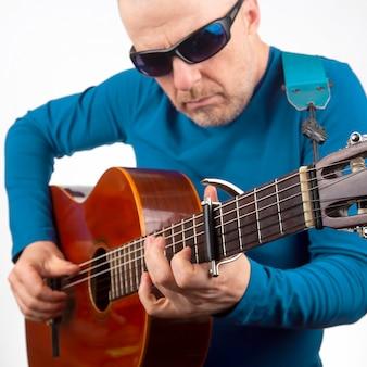Mann spielt die klassische gitarre auf einem weißen hintergrund. musikalische kreativität. saitenmusikinstrument