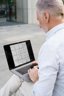 Mann spielt ein sudoku-spiel auf seinem laptop
