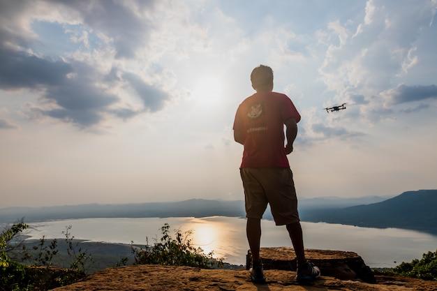 Mann spielt mit der drohne. silhouette gegen den sonnenuntergang himmel