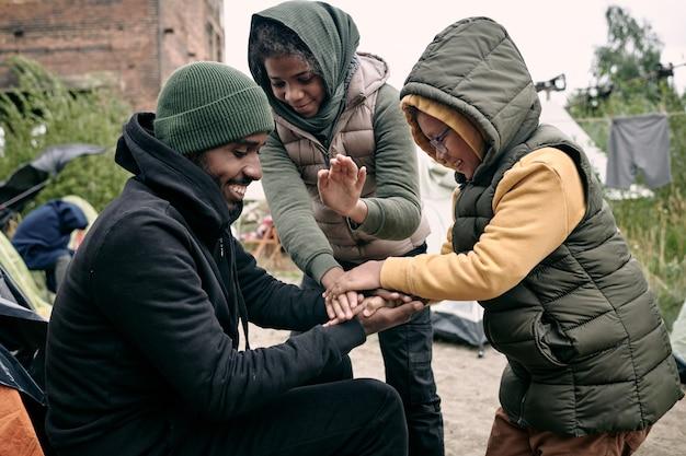 Mann spielt mit kindern im flüchtlingslager