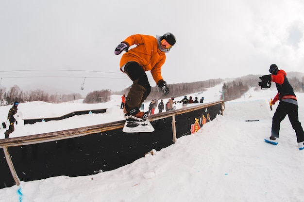 Mann spielt mit snowboard im winter