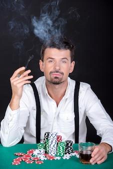 Mann spielt poker im kasino und raucht.