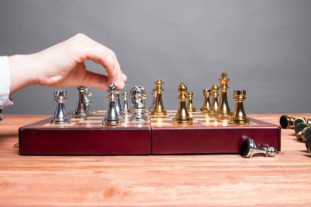 Mann spielt schach an einem holztisch.