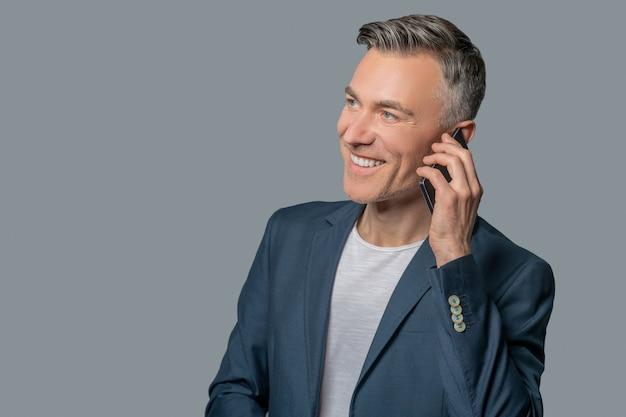 Mann spricht gut gelaunt am smartphone