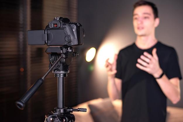 Mann spricht in die kamera und zeichnet sich in einem vlog auf. von zu hause aus arbeiten. junger ersteller von inhalten