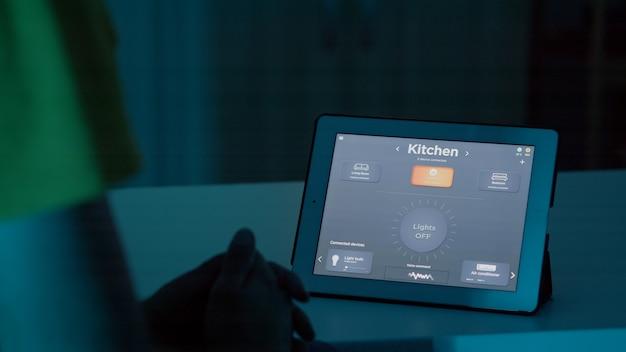 Mann spricht mit sprachassistent auf tablet im smart home automation system