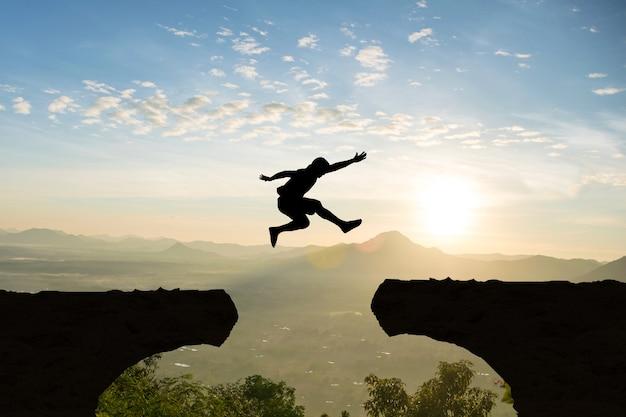 Mann springen gebirgsklippen-sonnenlicht über schattenbild
