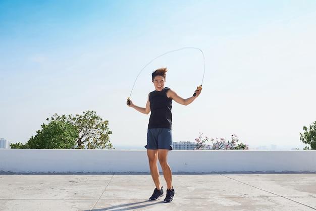 Mann springt auf das springseil. junge asiatische männer mit nacktem oberkörper, die draußen auf dem seilspringen springen