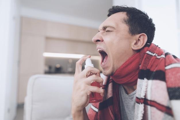 Mann spritzt in seine kehle medizinisches spray für seine kehle