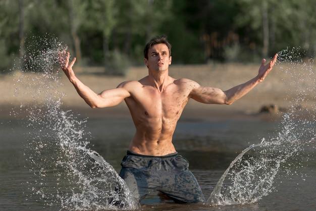 Mann spritzwasser am strand