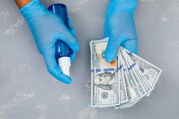 Mann sprüht desinfektionsmittel auf banknoten.