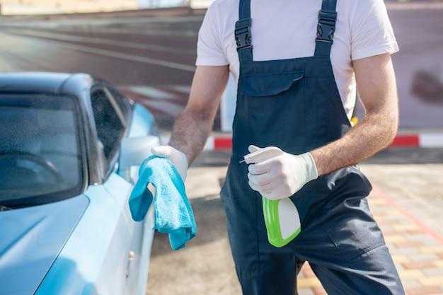 Mann sprüht reinigungsmittel auf serviette