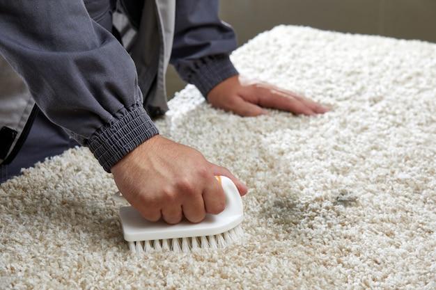 Mann sprüht waschmittel auf grauen teppich, um flecken im professionellen reinigungsservice zu entfernen