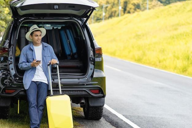 Mann stand mit handy und gepäck im auto