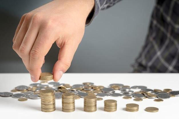 Mann stapelt münzen in abnehmender packung