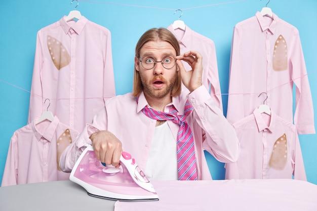 Mann starrt fassungslos bügeleisen tücher kann nicht an etwas glauben hält hand auf brille posen in waschküche mit gebügelter kleidung hängt blau
