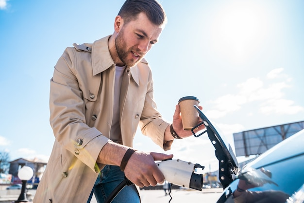 Mann steckt stecker ins elektroauto