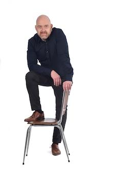 Mann stehend mit einem stuhl im weißen hintergrund, fuß über dem stuhl