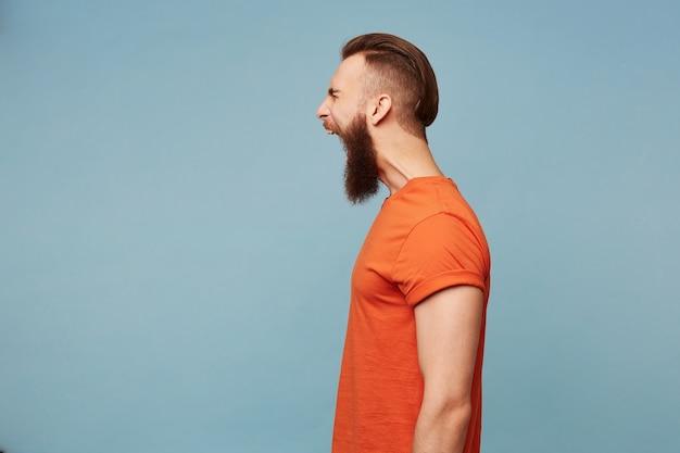 Mann stehend profil seitwärts schreit laut, gesichtsausdruck des zorns, isoliert auf blau