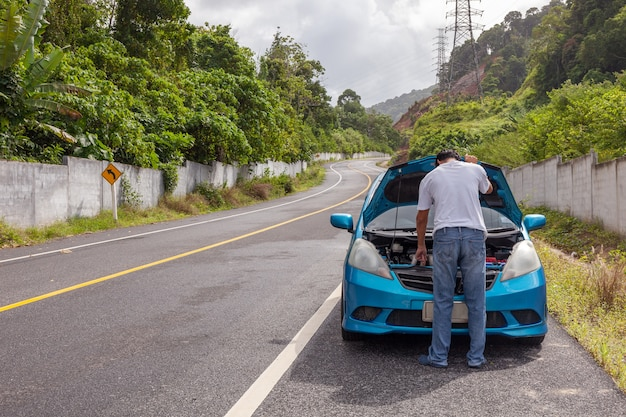 Mann stehend überprüfen motorunfallauto auf der straße mit motorstörungsauto in der mitte der straße.