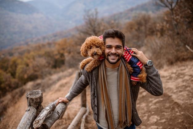 Mann stehend und hält hund auf schultern in der natur.