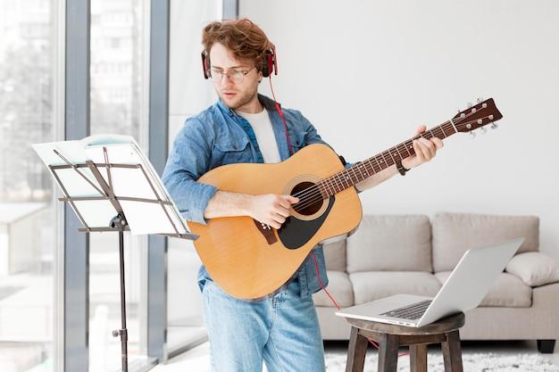 Mann stehend und versuchend, das musikinstrument zu lernen