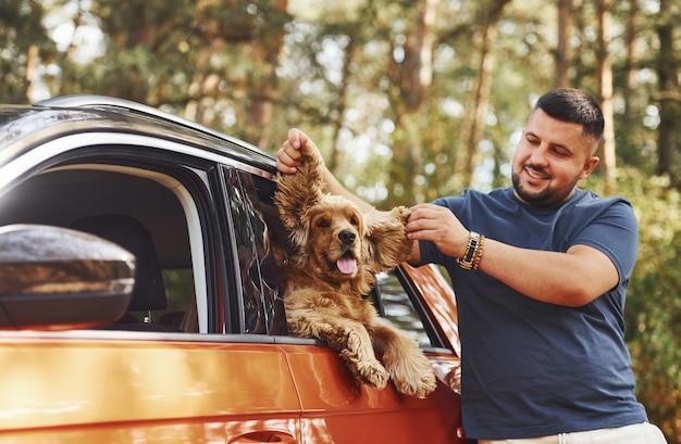 Mann steht am auto im wald. netter hund im fahrzeug schaut durch das fenster.