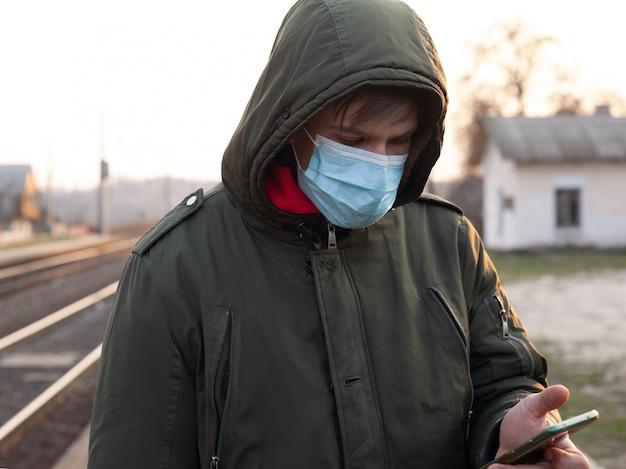 Mann steht an der station in einer medizinischen einwegmaske, die in händen telefonepidemie-atemwegserkrankung coronavirus-grippe hält. flash covid-19 des öffentlichen verkehrs und der grenze aufgrund von quarantäne.