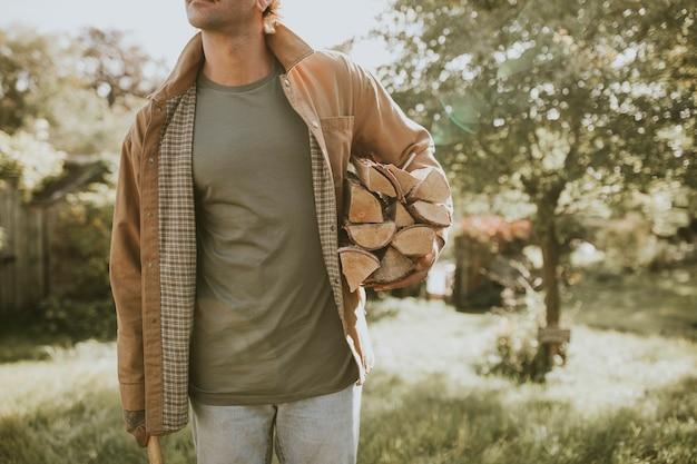 Mann steht mit axt und gehacktem bauholz und baumstumpf auf einem bauernhof