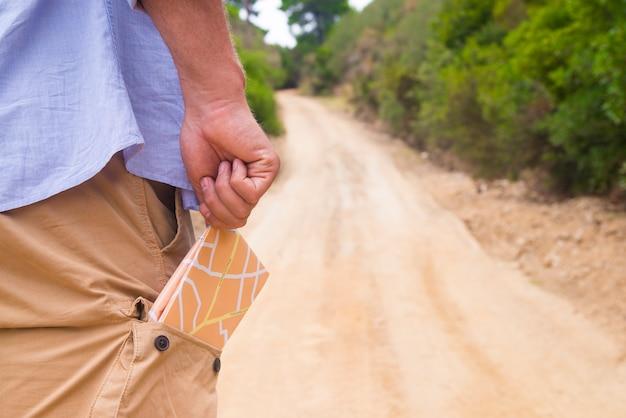 Mann steht mit reisekarte in der hinteren tasche