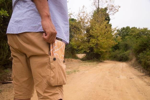 Mann steht mit reisekarte in der tasche
