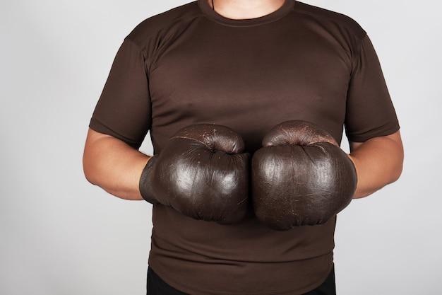 Mann steht, tragend sehr alte weinlesebraun-boxhandschuhe auf seinen händen