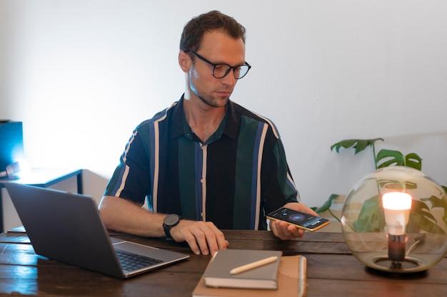 Mann steuert eine intelligente lampe mit seinem telefon
