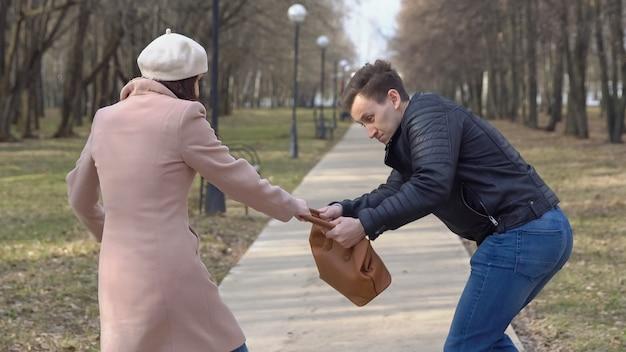 Mann stiehlt die tasche einer frau von einer bank im park.