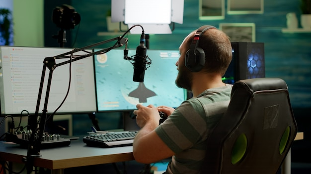 Mann-streamer, der space-shooter-videospiele mit professioneller rgb-tastatur und drahtlosem joystick spielt. profi-gamer, der während des online-turniers beim streaming-chat ins mikrofon spricht