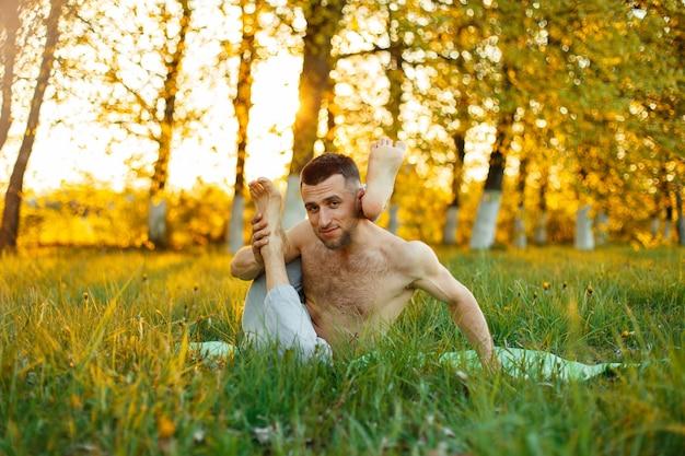Mann streckt die muskeln und praktiziert yoga im park bei sonnenuntergang. gesunder lebensstil