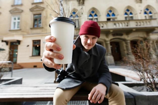 Mann streckt seine hand mit der tasse kaffee aus, die auf der bank sitzt