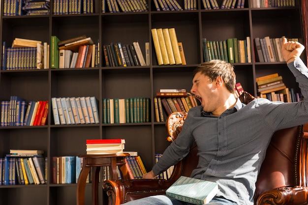 Mann streckt sich und gähnt, als er von einem nickerchen in einem bequemen sessel in einer bibliothek aufwacht