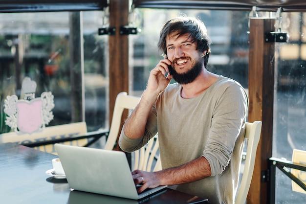 Mann / student, der computer im café verwendet und am telefon spricht