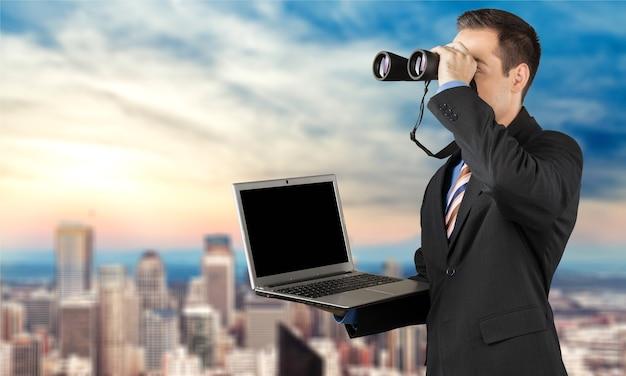 Mann sucht mit fernglas und laptop