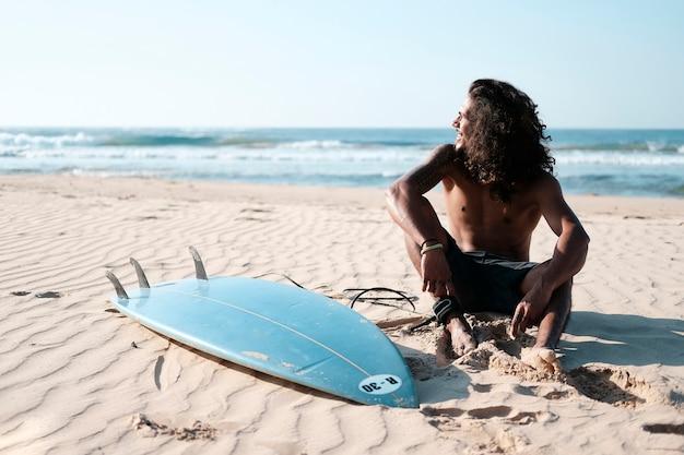 Mann-surfer, der am surfbrett am sandstrand sitzt